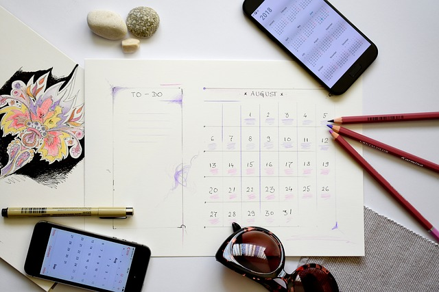 a photo of a calendar sheet with pencils, 2 smart phones, and a pen